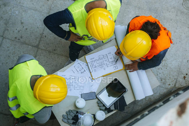 Group of workers talking about the project on a working table, seen from above. — Stock Photo