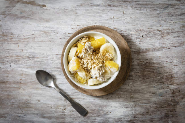 Top view of oat flakes with sliced banana and yogurt in bowl — Stock Photo