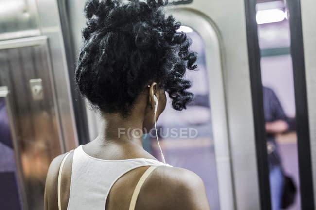 Portrait recadré de femme avec des écouteurs debout dans le métro train — Photo de stock