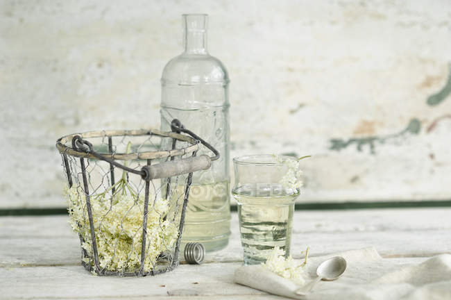 Glass bottle and glass of elderflower sirup and elderflowers in wire basket — Stock Photo