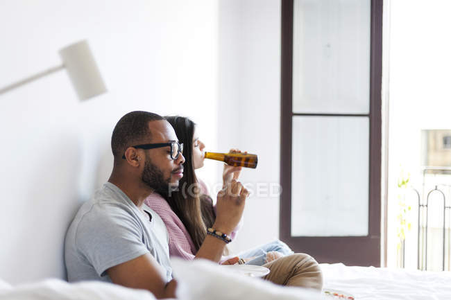 Portrait of young couple sitting with food and drink on bed — Stock Photo