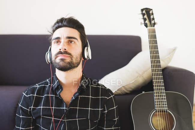 Hombre en auriculares y guitarra de sofá - foto de stock