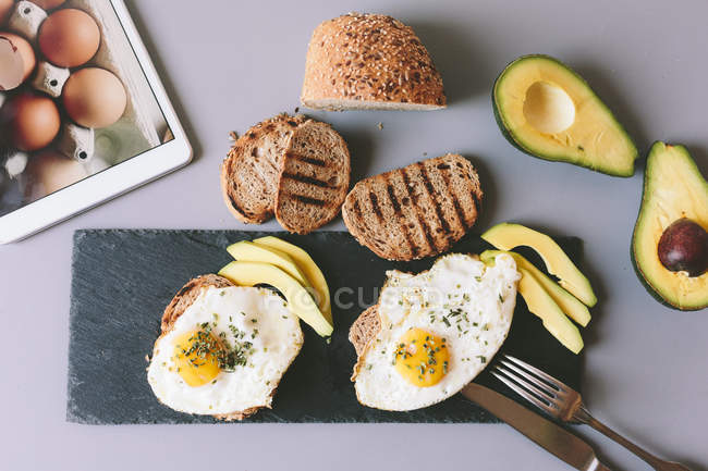 Top view of fried eggs with toasts and avocado — Stock Photo