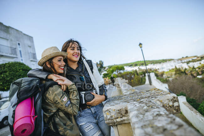 Young traveling women laughing and looking at view — Stock Photo