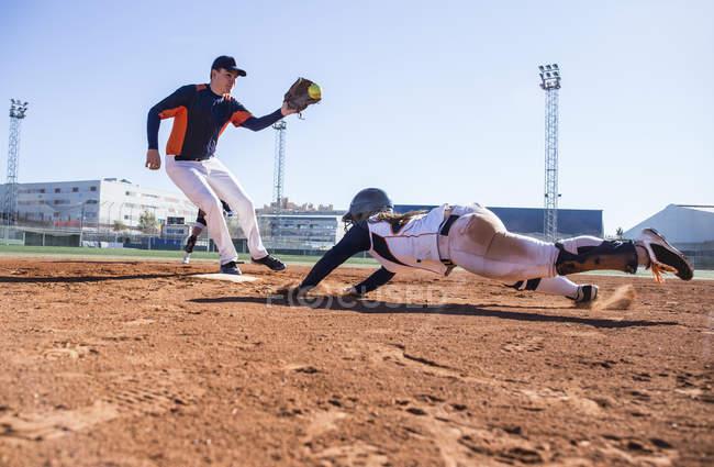 Baseball player sliding to the base during a baseball game — Stock Photo