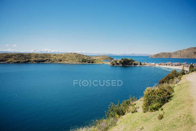 Isla del sol, lago Titicaca, Bolívia. Comunidad Challapampa nas margens do lago titicaca com neve Andes no fundo — Fotografia de Stock
