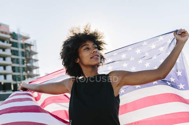 Retrato de jovem segurando bandeira americana — Fotografia de Stock