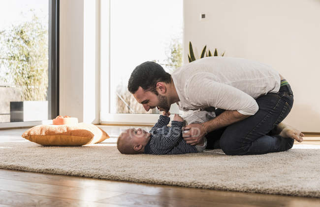 Father changing diapers and playing with baby son — Stock Photo