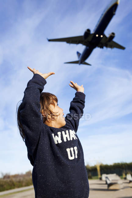 Portrait of boy raising hands to airplane and looking at it — Stock Photo