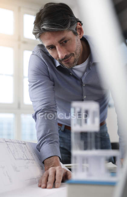 Man looking at architectural model in office — Stock Photo