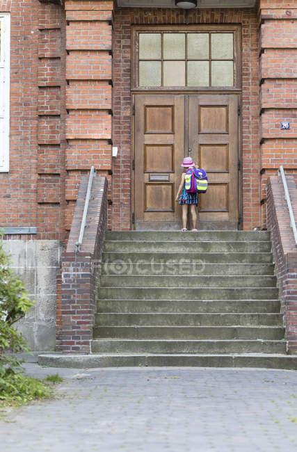 Menina com bolsa escola, em frente à entrada da escola — Fotografia de Stock