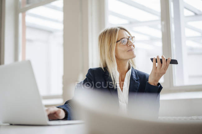Businesswoman using laptop and cell phone — Stock Photo