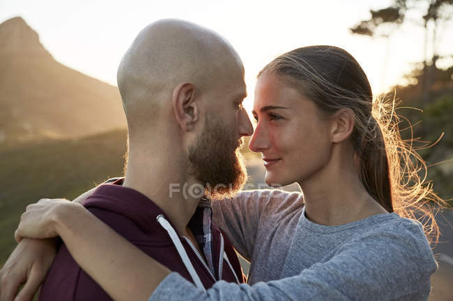 Young couple in love standing face to face at backlit — Stock Photo