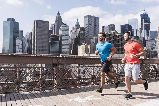 США, Нью-Йорк, Бруклинский мост, два молодых человека бегают трусцой, вид на городской пейзаж на заднем плане — стоковое фото