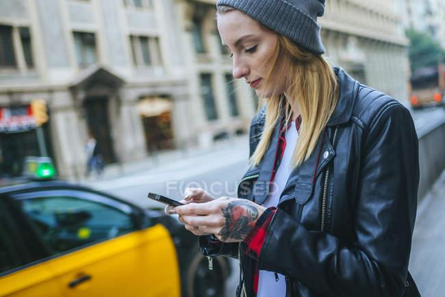 Mujer joven caminando por la calle mientras usa su teléfono móvil . - foto de stock