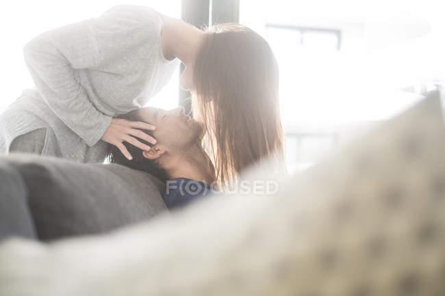 Femme se penchant sur l'homme en rétro-éclairé — Photo de stock