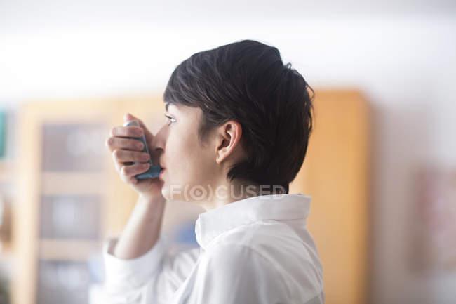 Jovem Mulher usando inalador — Fotografia de Stock