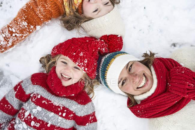 Mère et filles couchées sur la neige, s'amusant — Photo de stock