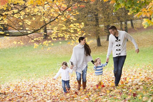 Família feliz com duas meninas andando em folhas de outono — Fotografia de Stock