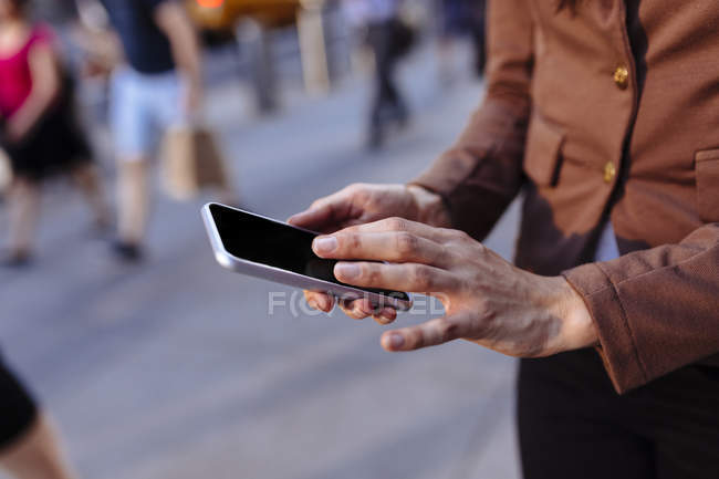 Female hands holding smartphone on city street — Stock Photo
