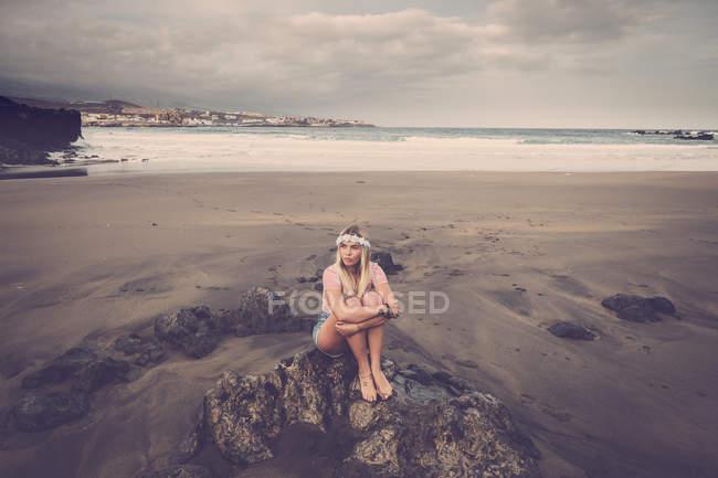 Іспанія, Тенеріфе, молода жінка, сидячи на скелі на пляжі — стокове фото
