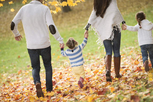 Rear view of happy family with two girls walking in autumn leaves — Stock Photo