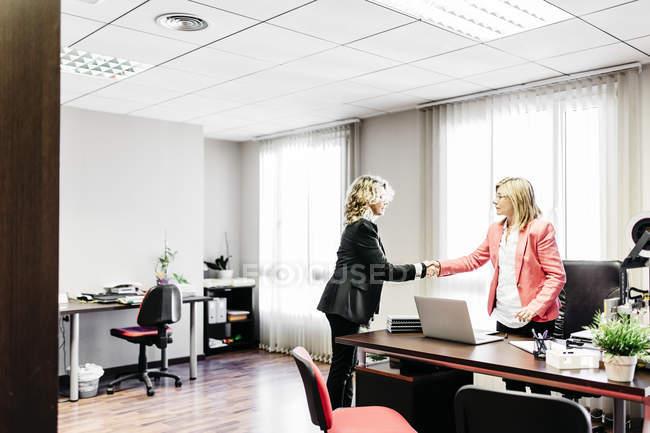 Две деловые женщины пожимают руки в офисе — стоковое фото