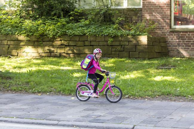 Menina a sorrir com saco de escola, andar de bicicleta na calçada — Fotografia de Stock