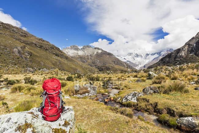 Peru, Andes, Cordilheira Blanca, Parque Nacional de Huascarán, mochila na rocha com vista para o Nevado Huascarán — Fotografia de Stock