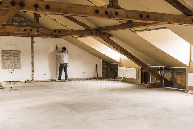 Portrait of young man measuring attic wall — Stock Photo