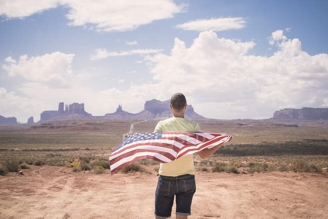 USA, Utah, man with American Flag looking at Monument Valley — Stock Photo