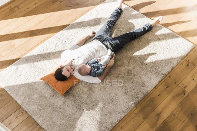 Спляча батько та дитина сина, лежачи на килимі вдома — стокове фото