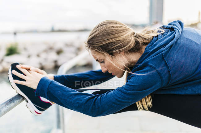 Young woman stretching and warming up for training at the beach — Stock Photo