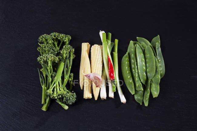 Верхний вид брокколи с гороховыми стручками, луком и кукурузой на черном фоне — стоковое фото