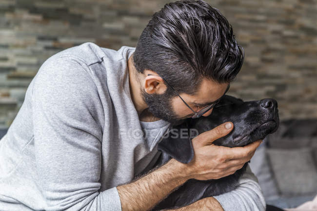 Cropped portrait of man petting black dog — Stock Photo