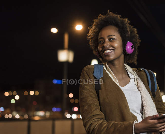 Sorrindo jovem com fones de ouvido esperando na parada de bonde — Fotografia de Stock