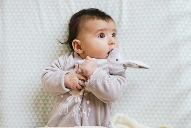 Baby girl lying on crib and biting a stuffed rabbit — Stock Photo