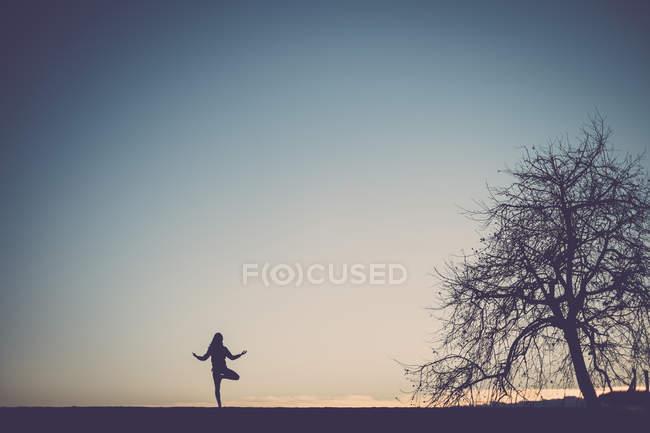 Silhouette einer Frau beim Yoga, Sonnenuntergangshimmel im Hintergrund — Stockfoto