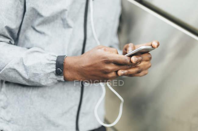 Afroamericano jogger usando smartphone - foto de stock