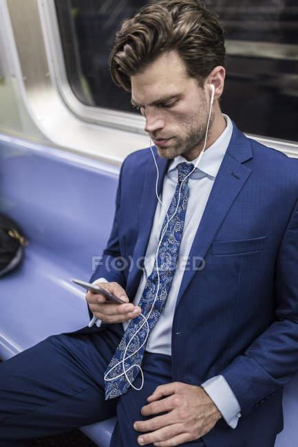 Портрет предпринимателя с помощью смартфона с earbuds в метро — стоковое фото