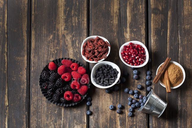 Different berries and seeds in bowls on wooden background — Stock Photo