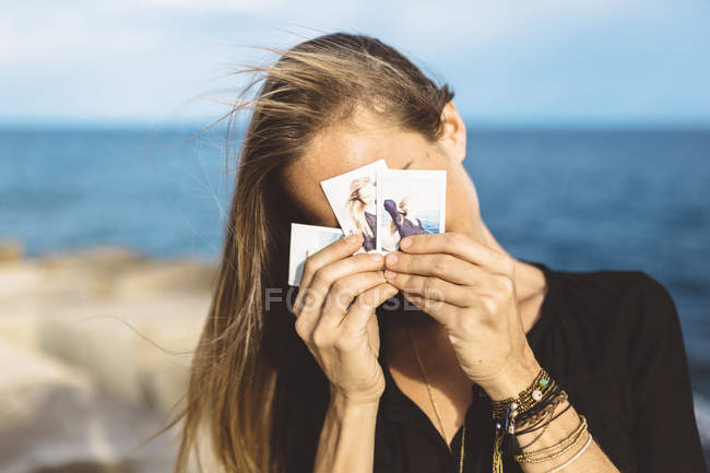 Young woman covering face with instant photos of herself — Stock Photo