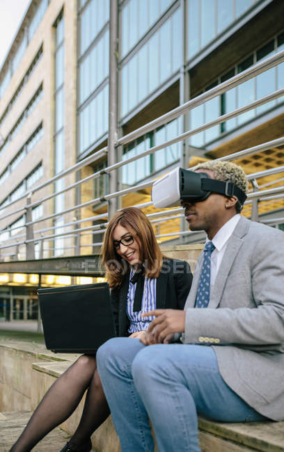 Young businessman and woman using VR goggles in front of office building — Stock Photo
