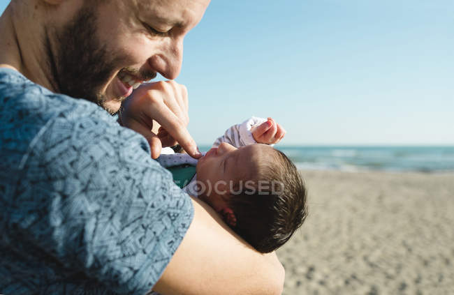 Father with newborn baby girl standing on the beach — Stock Photo