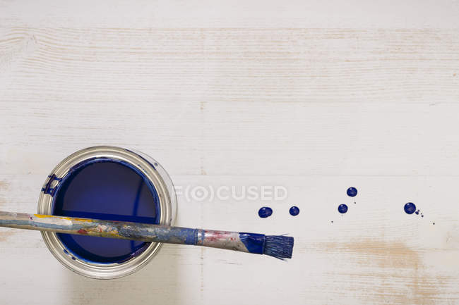 Used paint brush on paint tin with blue varnish — Stock Photo