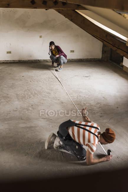 Portrait of young couple measuring attic floor — Stock Photo