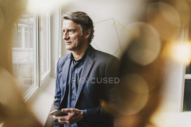 Uomo d'affari maturo che osserva dalla finestra con smartphone — Foto stock