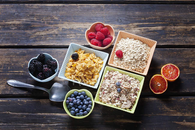 Elevated view of oat and corn flakes with berries and red orange — Stock Photo