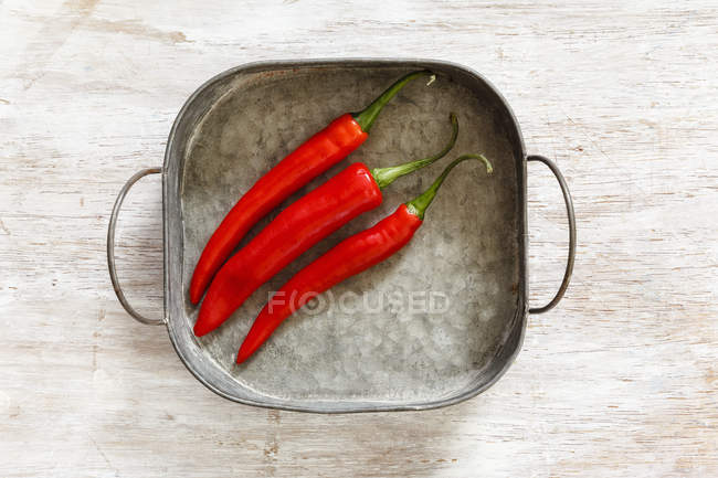 Top view of three red chilli peppers in metal tray on wooden surface — Stock Photo