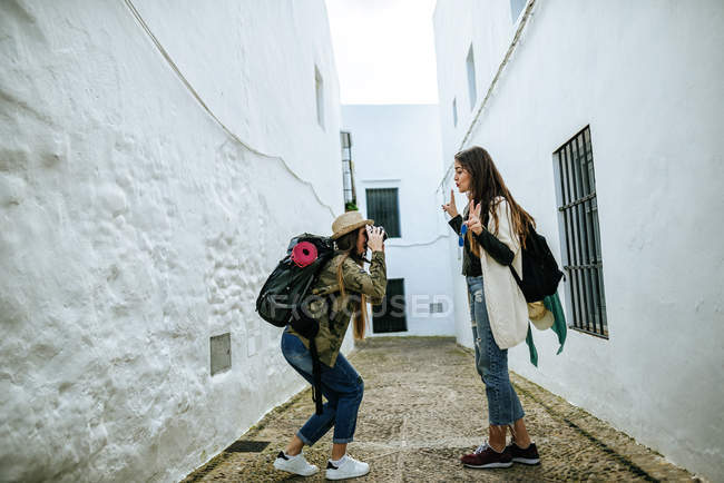 Young traveling women taking photos on white street — Stock Photo